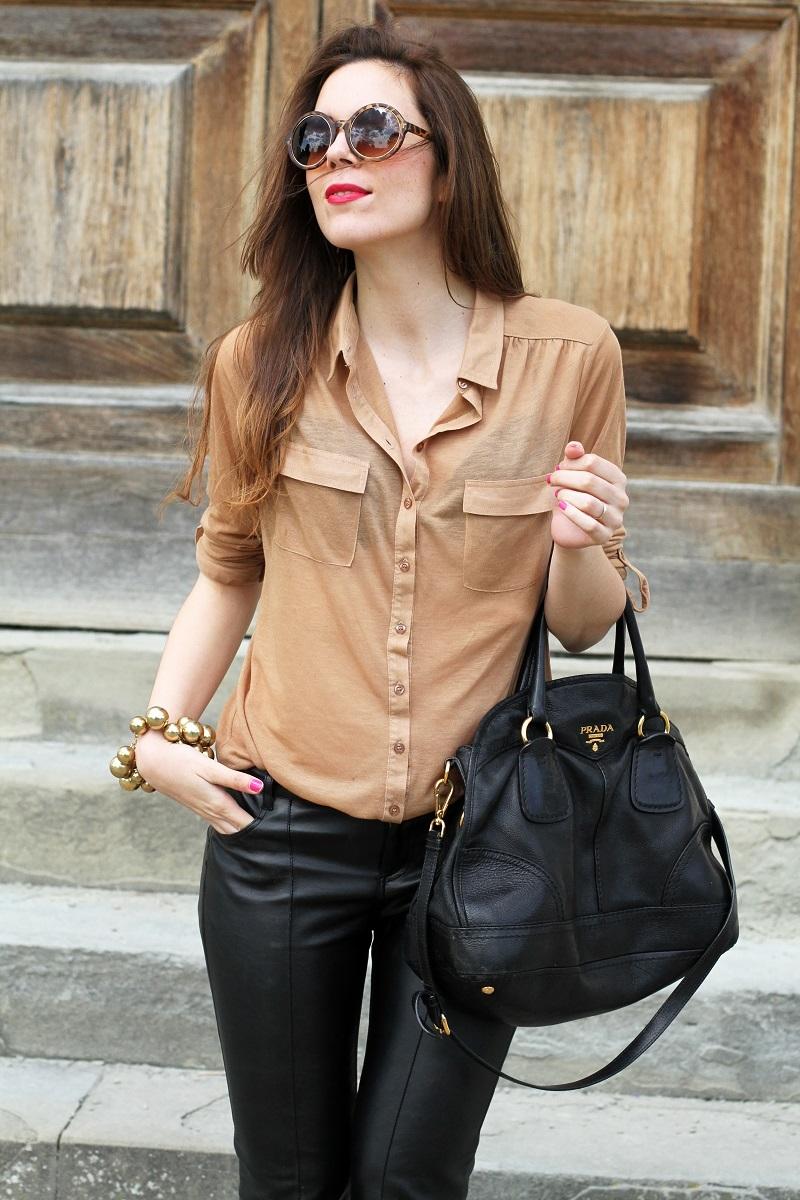 pantaloni di pelle nera | pelle | camicia beige | camicia marrone | braccialetto grande | occhiali da sole rotondi | smalto fucsia | occhiali da sole | fashion | moda | outfit | look | streetstyle | irene colzi