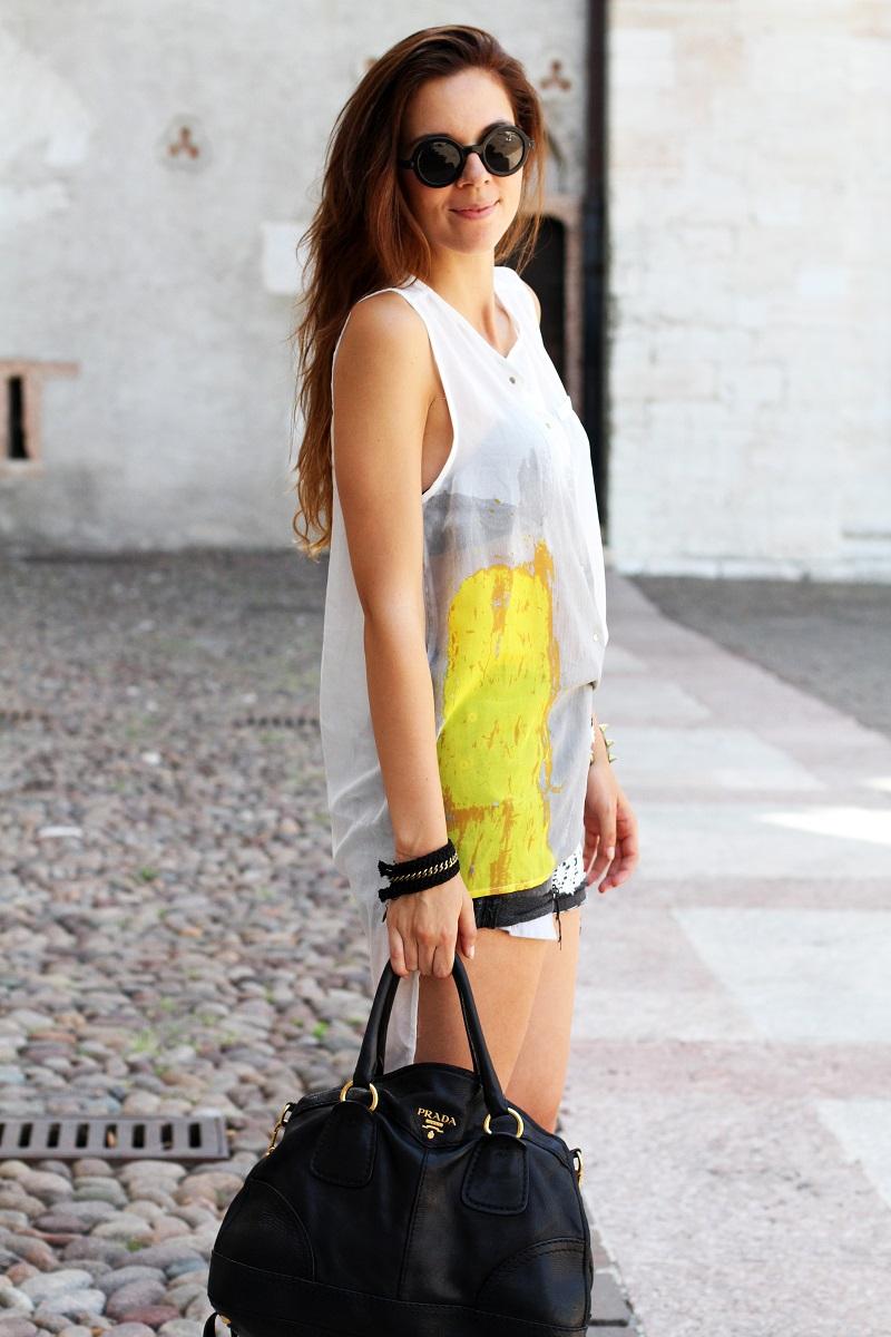 trento come sfondo di un outfit look casual femminile con shorts levis vintage tagliati camicia senza maniche bianca occhiali da sole rotondi e borsa prada nera 3